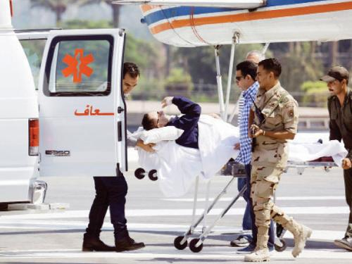 Medics and army personnel escort former Egyptian president Hosni Mubarak, 86, from a helicopter ambulance after landing at the Maadi Military Hospital following a hearing in his retrial in Cairo, Wednesday.