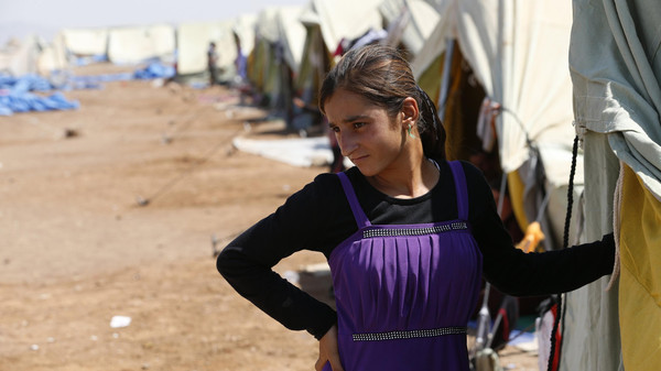 A displaced girl from the minority Yazidi sect, who fled the violence in the Iraqi town of Sinjar, stands at Nowruz refugee camp in Qamishli, northeastern Syria on the border with Kurdistan August 16, 2014.