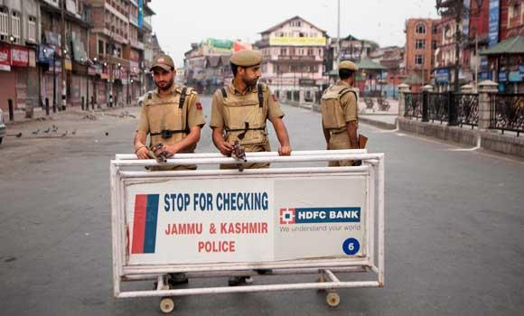 Indian policemen stand guard at a temporary check point during curfew in Srinagar, India, in this Aug. 15, 2014 photo.