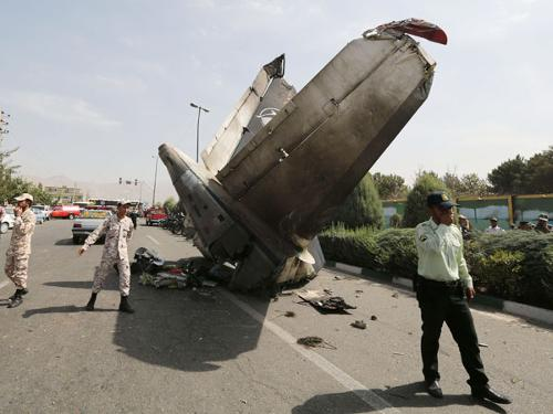 Iranian Revolutionary Guards and security forces stand next to the remains of a plane that crashed near Tehran's Mehrabad airport on Sunday.