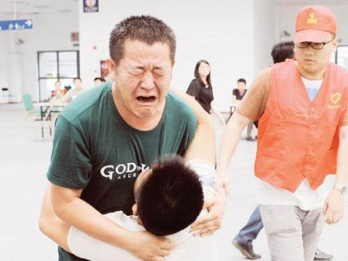 Family members cry at a caring center for relatives of victims of a factory explosion, in Kunshan, Jiangsu province, on Sunday.