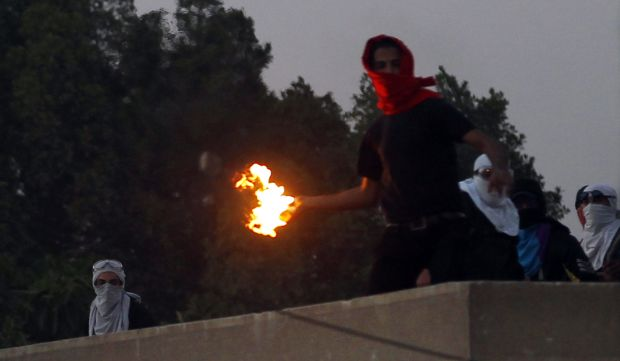 A masked student of Al-Azhar University throws a Molotov cocktail at riot police and residents during clashes outside the university campus in Cairo's Nasr City district on December 27, 2013.
