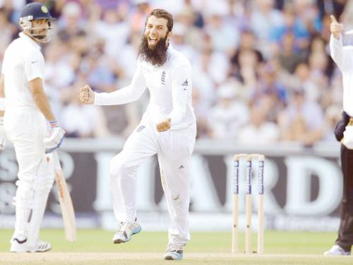 England's Moeen Ali (C) celebrates after dismissing India's Cheteshwar Pujara during the fourth cricket Test match at Old Trafford cricket ground in Manchester Saturday.