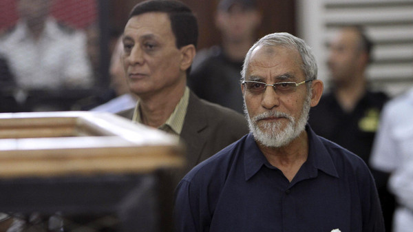 Muslim Brotherhood's Supreme Guide Mohamed Badie (R) looks on during his trial at a court in Cairo, in this May 18, 2014 file picture.