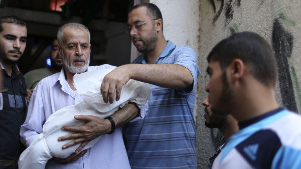 A relative of the wife of Hamas's military leader, Mohammed Deif, and his infant son Ali, whom medics said were killed in Israeli air strikes, carries Ali's body during their funeral in the northern Gaza Strip August 20, 2014.