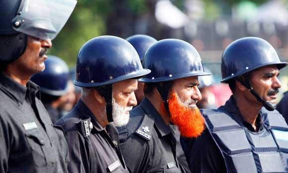 Policemen stand guard against supporters of Mohammad Tahir ul-Qadri, Sufi cleric and leader of political party Pakistan Awami Tehreek, during the Revolution March to the parliament house in Islamabad on Wednesday.