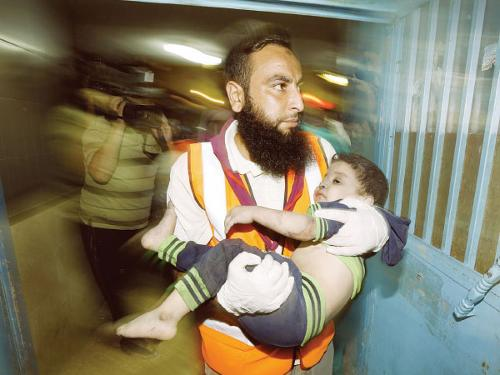 Palestinian doctor carries a wounded child at the hospital following an Israeli air strike on a house in Gaza City, late on Tuesday.