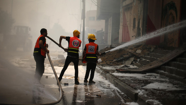 Palestinian firefighters participate in efforts to put out a fire at the scene of what witnesses said was an Israeli air strike on a house in Gaza City August 23, 2014.