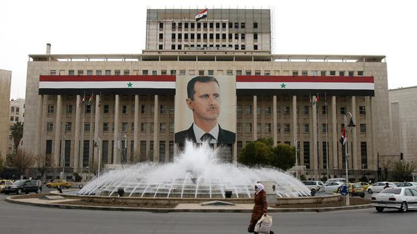 A woman walks past the central bank building decorated with a banner of President Bashar al-Assad in Damascus in this Feb. 28, 2012 file photo.