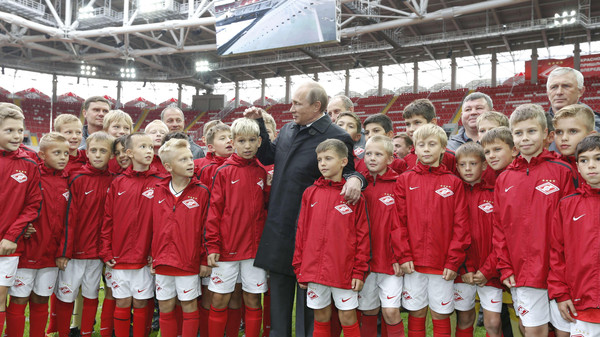 Russian President Vladimir Putin talks to young football players during a visit to Spartak's stadium Otkritye Arena in Moscow, on August 27, 2014.