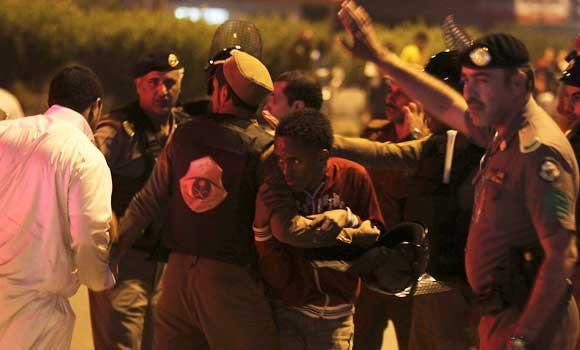 In this November 9, 2013 file photo shows members of Saudi security forces detain Ethiopian workers during a riot in Manfouha, southern Riyadh.