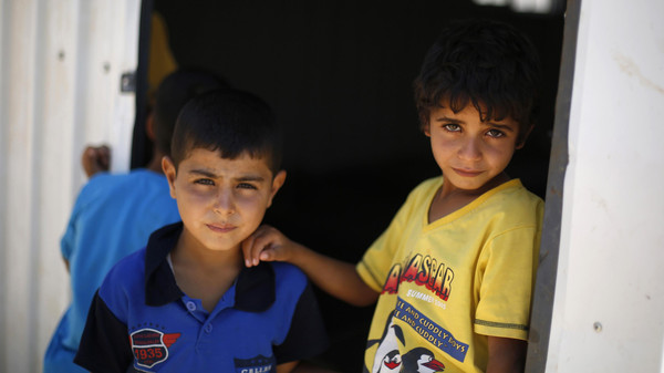 Syrian refugee children stand in front of their family residence at Azraq refugee camp near Al Azraq, east of Amman.