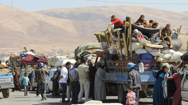 Syrian refugees, fleeing the recent fighting in Arsal, wait by trucks in Majdel Anjar in the Bekaa valley, near the Lebanese border with Syria August 8, 2014.