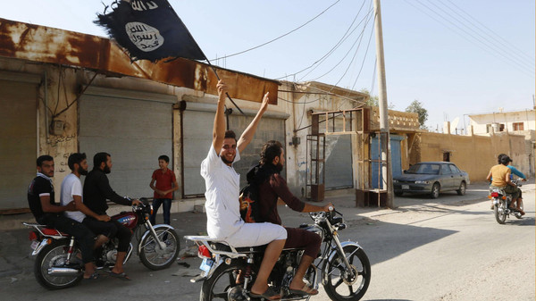 A resident of Tabqa city touring the streets on a motorcycle waves an Islamist flag in celebration after ISIS militants took over Tabqa air base, in nearby Raqqa city August 24, 2014.