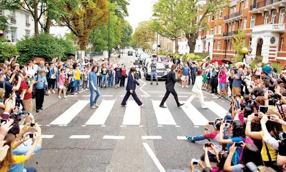 "The cast of the West End Beatles musical show ""Let it Be"" pose for photographers by attempting to recreate the cover photograph of the Beatles album ""Abbey Road"" in London."