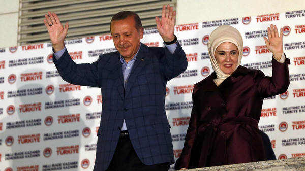 Turkey's Prime Minister Tayyip Erdogan and wife Ermine wave hands to supporters as they celebrate his election victory in front of the party headquarters in Ankara August 10, 2014.