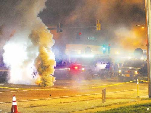 Law enforcement fires tear gas on protesters on West Florissant Road in Ferguson, Missouri, on Sunday night.