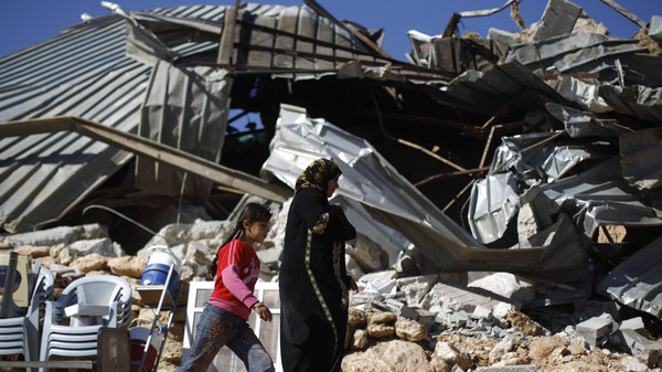 Palestinians walk past a structure after it was demolished by Israeli bulldozers in Khirbet Al-Taweel village near the West Bank City of Nablus April 29, 2014.