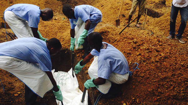 Volunteers lower a corpse, which is prepared with safe burial practices to ensure it does not pose a health risk to others and stop the chain of person-to-person transmission of Ebola, into a grave in Kailahun.