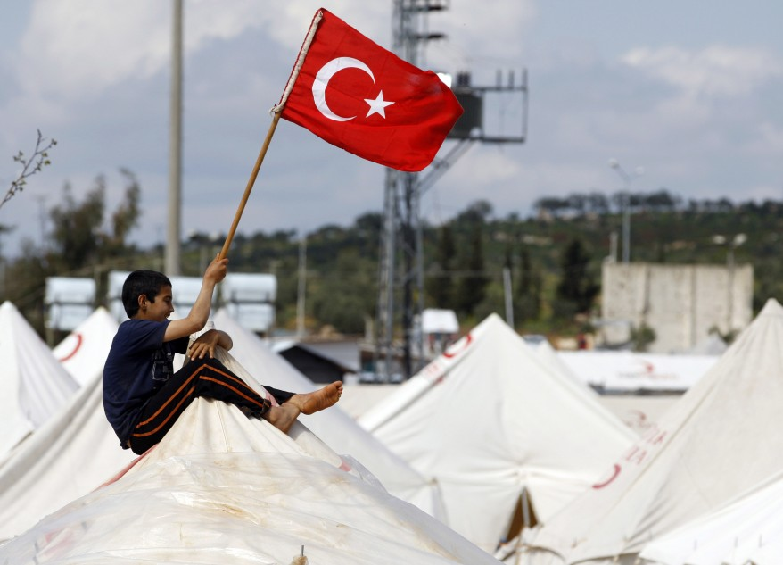 A Syrian refugee waves a Turkish flag as he sits atop a tent at the Reyhanli refugee camp in Hatay province on the Turkish-Syrian border.