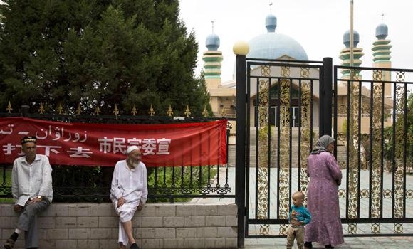 In this photo taken July 17, 2014, Uighur residents gather outside a mosque in the city of Aksu in western China's Xinjiang province. In China's restive western province of Xinjiang, young men of the Uighur ethnic minority are not allowed to have beards.