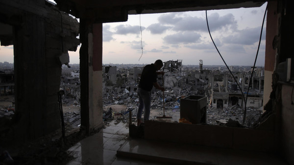 A Palestinian man cleans his house that witnesses said was heavy shelled by Israel during the offensive, in the Shejaia neighborhood east of Gaza City.