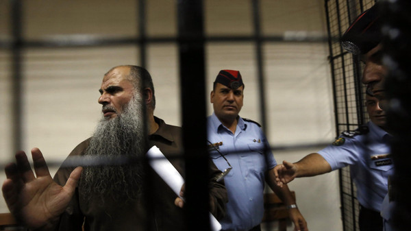 Radical Muslim cleric Abu Qatada (L) speaks to the media after his hearing at the State Security Court in Amman September 7, 2014.