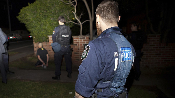 An Australian Federal Police officer and a New South Wales policeman stand near a suspect (L) who was detained during a raid on a house in western Sydney earlier this month.