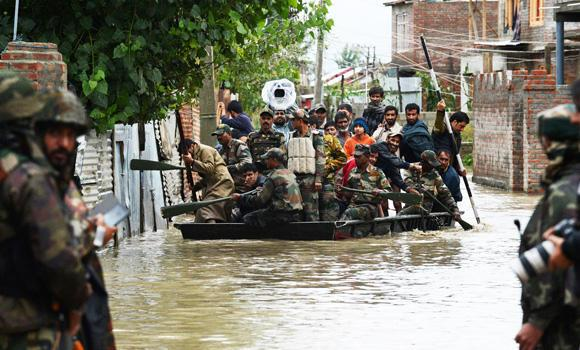 Indian soldiers paddle a raft as they assist Kashmiri residents during flood rescue operations in the outskirts of Srinagar on Friday. Flooding has hit hundreds of villages across the picturesque Kashmir Valley in the country's north, leaving at least 29 people dead, and forcing the closure of schools and some roads.