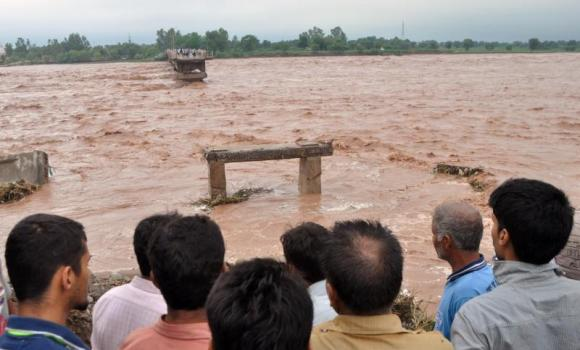 Indian villagers look on at a missing section of a bridge across the overflowing Tawi river that was swept away as flooding continues in the Mandal area of Jammu on September 6, 2014.