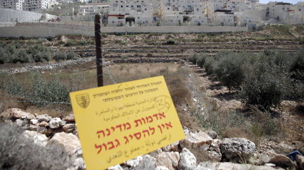 An official Israeli sign placed in the West Bank near the Israeli Beitar Illit (back) settlement states that the area is state land and trespassing is not allowed, near the Palestinian village of Wadi Fukin, on September 4, 2014.
