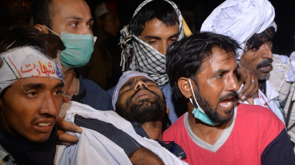 Pakistani opposition supporters carry a wounded protester following clashes with security forces near the prime minister's residence in Islamabad on August 30, 2014.