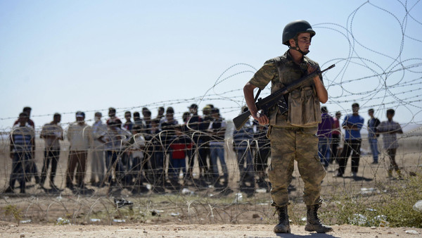 A Turkish soldier stands guard as Syrian Kurds wait behind the border fence near the southeastern town of Suruc in Sanliurfa province, September 21, 2014.