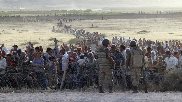Turkish soldiers stand guard as Syrians wait behind the border fences near the southeastern town of Suruc in Sanliurfa province, September 18, 2014.