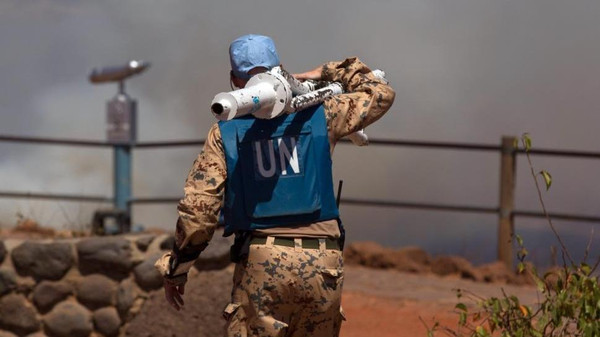 A U.N. peacekeeper carries equipment at the Syrian-Israeli border.