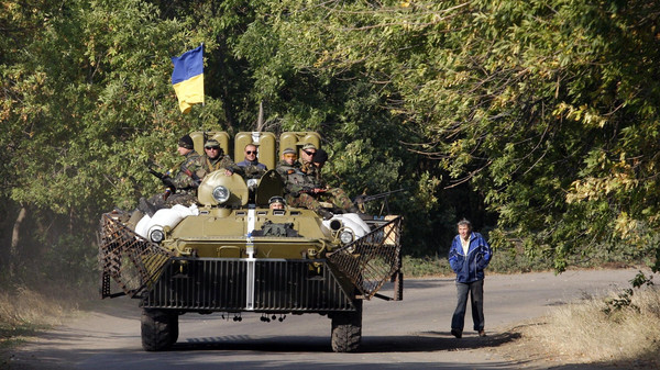 A man looks on as Ukrainian servicemen sitting atop of an Armoured Personnel Carrier drive past during a patrol in Donetsk region on September 15, 2014.