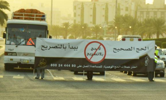 Volunteers hold banners warning people against performing Haj without a permit.