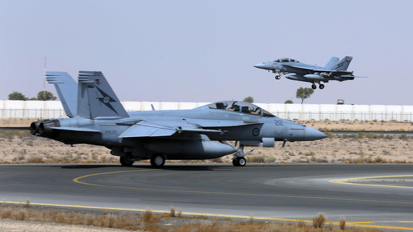 A Royal Australian Air Force (RAAF) F/A-18F Super Hornet takes off as another taxis along the runway as they start their first combat mission over Iraq.
