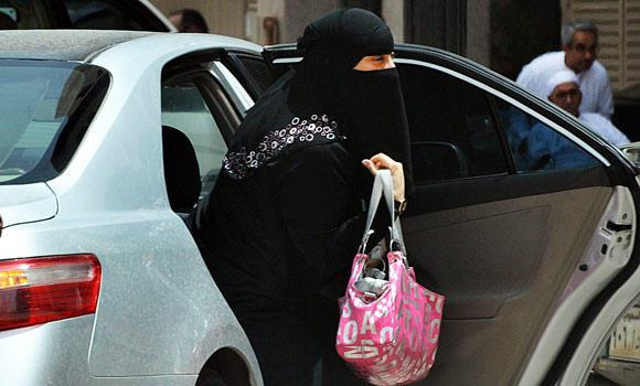 A Saudi woman gets out of a car after being given a ride by her driver in Riyadh, in this May 26, 2011 file photo.