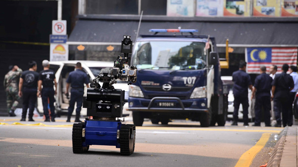 A bomb disposal robot (front) is deployed after a grenade exploded in front of the Sun Complex in Jalan Bukit Bintang, Kuala Lumpur on October 9, 2014.