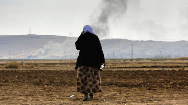 A female Kurdish refugee tries to call relatives who are still trapped in Kobane.