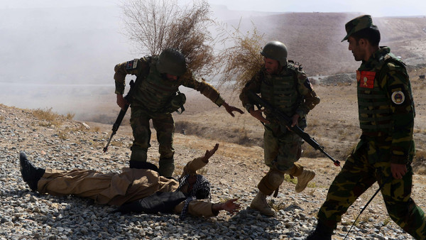 Afghan National Army (ANA) solders arrest a fake Taliban fighter as they take part in a training exercise at the Afghan National Military training center (KMTC) in Kabul on Oct. 22, 2014.