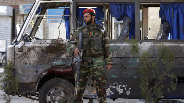 An Afghan national army soldier stands guard next to a bus which was hit by a remote-controlled bomb at the site of an incident in Kabul October 21, 2014.