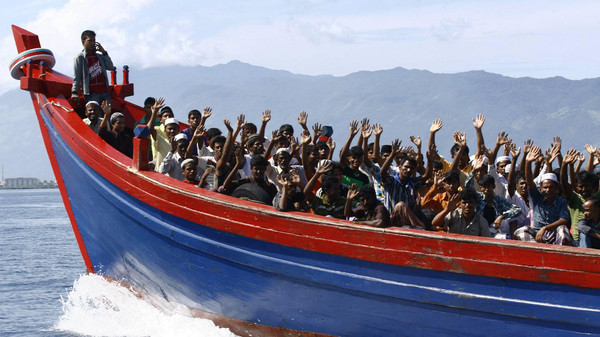 Ethnic Rohingya refugees from Myanmar wave as they are transported by a wooden boat to a temporary shelter in Krueng Raya in Aceh Besar in this April 8, 2013 file photo.