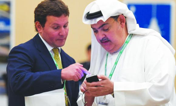 Investors look at a mobile phone as they attend the fourth Annual Solar Arabia Summit in Riyadh.