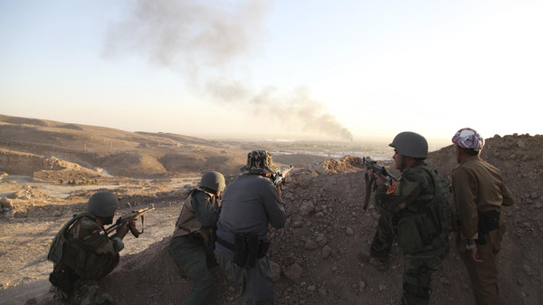 Iraqi Kurdish Peshmerga troops watch as smoke billows from the town of Makhmur during clashes with ISIS militants August 9, 2014.
