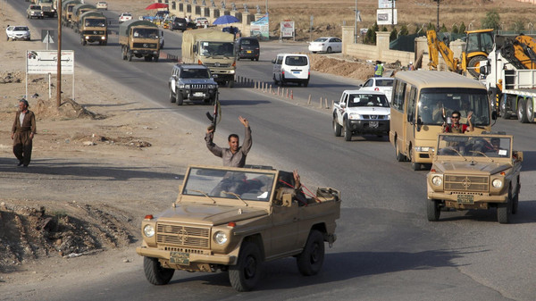 A convoy of Kurdish peshmerga fighters drive through Arbil after leaving a base in northern Iraq, on their way to the Syrian town of Kobane,Oct. 28, 2014.