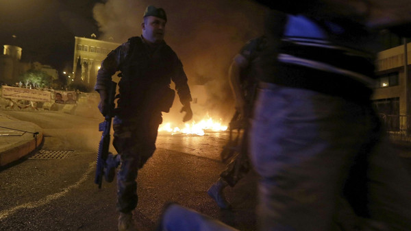 Lebanese Army soldiers run in front of burning tyres during a protest by relatives of soldiers demanding the release of soldiers captured by Islamist militants in Arsal.