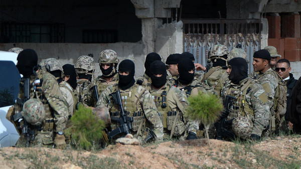 Members of the Tunisian military stand in a group during an operation against gunmen in the town of Oued Ellil near the Tunisian capital Tunis on Oct. 24, 2014.