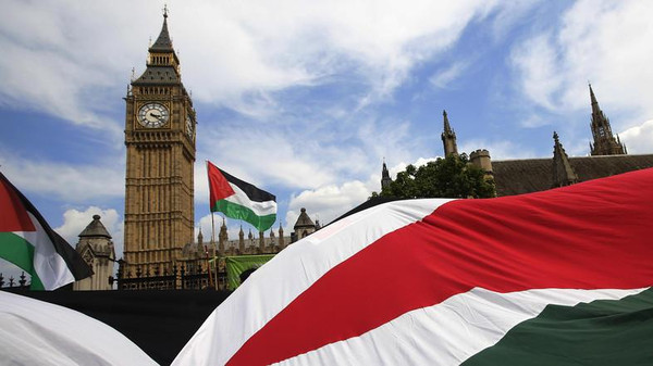 Demonstrators carry Palestinian flags as they protest outside the Houses of Parliament in London.